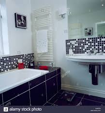 black white mosaic tiles above bath and basin in modern white