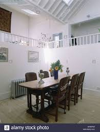 wood table and chairs in modern loft conversion dining room with