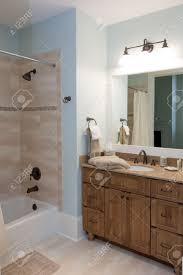 modern bathroom with wood cabinets and stone tile shower stock