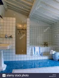 aquamarine blue tiled floor in modern white tiled tuscan bathroom