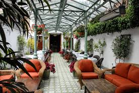 our partners alliance francaise de san francisco the inner courtyard is an oasis featuring mosaic like tile flooring a vaulted pressed tin ceiling tropical plants and plush rattan furniture