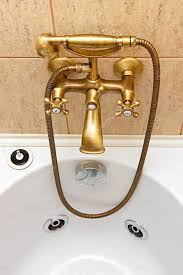 vintage bathtub faucet and ceramic tiles in background u2014 stock