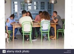 young adult friends talk at a dining room table full length stock stock photo young adult friends talk at a dining room table full length