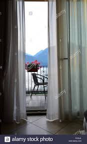 a gentle breeze wafts the curtains of a hotel room with balcony