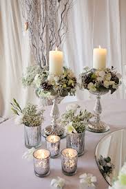 silver centerpieces silver glasses with candles combined with silver vases with white