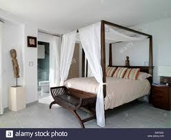white drapes on simple four poster bed in white coastal bedroom