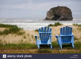 Chairs On A Beach Two Blue Adirondack Chairs On A Grassy Beach With Rock Formations