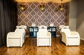 old fashinoned hairdressers and there salon potos velvet flocked wallpaper brass light fixtures and navy painted
