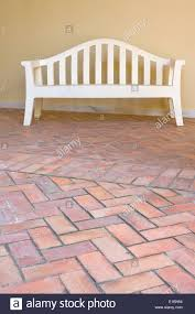 white wooden bench over red brick floor of an spanish traditional