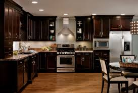 glass countertops dark kitchen cabinets with floors lighting