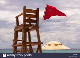 Red Flag Band Lifeguard Post At A Tropical Beach Stands Abandoned As Red Flag