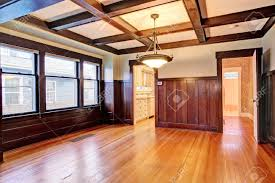 empty room with wood paneled walls and coffered ceiling american