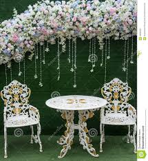 wedding backdrop green chair and table with fowers on green backdrop stock photo image