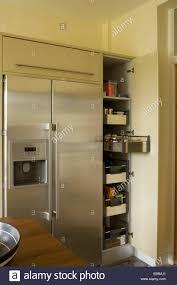 stainless steel american style fridge beside open larder cupboard
