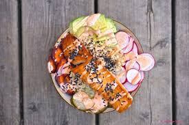 vegan sriracha mayo asian salmon and rice bowl with pickled cucumbers and sriracha mayo