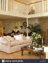 Small Mezzanine Bedroom by Cream Sofa And Indonesian Coffee Table With Vase Of White Lilies