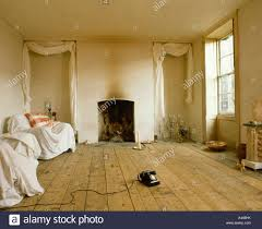 empty room with wooden floor and furniture covered with dustsheets