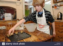 fair haired boy in a junior chef apron puts cookie dough onto a