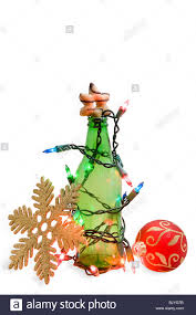 green beer bottle wrapped in christmas lights with ornaments and a