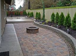 backyard paver patio connected to a concrete slab basketball court