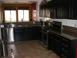 elegant black l shaped kitchen cabinets with rustic gray floor