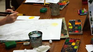 young woman artist draw pictrure with watercolor paints and brush