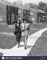 1950s homes 1950s man woman couple arm in arm walking down suburban sidewalk
