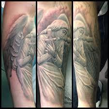 adorable black angel tattoo on arm tattoomagz