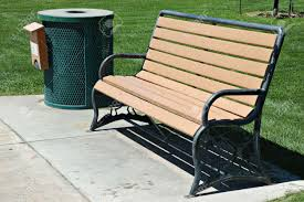 park bench and trash can with grass and sidewalk stock photo