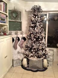 black tree with silver and white decorations decorated by