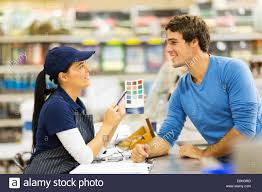 pretty paint store assistant helping customer choose paint color