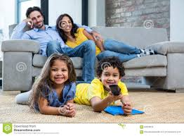 smiling family in living room looking tv stock photo image 62326018