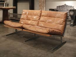 an aluminium and tan leather sofa by jorgen kastholm tables