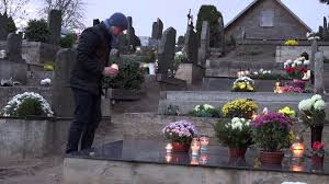 mourning man kneel on grave at cemetery and pray with burn candle