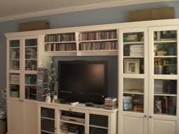 large white wooden bookshelves with glass door and storage