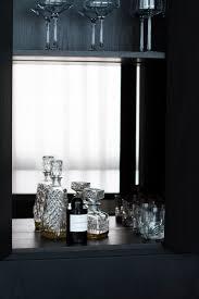 hidden bar in a stained oak kitchen with bronze mirror splash back