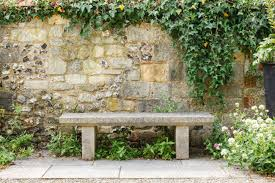 bench in a formal garden with an old stone wall stock photo