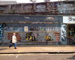 a london street artist paints swarms of bees on urban walls to bees 7