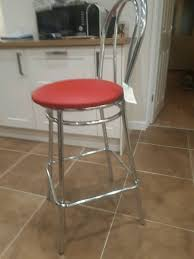 5 chrome bar stools with red leather imitation upholstery in