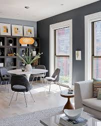 open plan gray room with round white dining table also gray modern