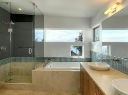frameless shower glass door beside drop in tubs in front bathroom