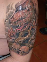 shoulder tattoo of dragon u0027s head with snake and two skulls