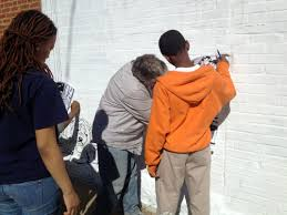 allowing the choir to paint mccammond helps a student with sketching the mural outlines on the wall