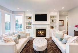 All White Family Room With Builtin White Shelving Around - Family room shelving