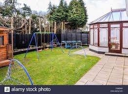 enclosed family rear garden with childrens swings football nets
