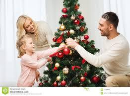 decorating christmas tree happy family decorating christmas tree at home stock photo image