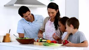 mother chatting to children at family breakfast at home in kitchen