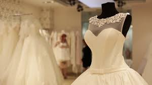 the wedding dress shop up of dummy with wedding dress shop assistant is helping