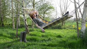young caucasian female resting lying on hammock among two poles