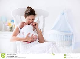 Rocking Chair For Breastfeeding Young Mother And Newborn Baby In White Bedroom Stock Photo Image